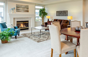 Living room with fireplace, small dining table, and living room furniture has wall-to-wall-white carpet