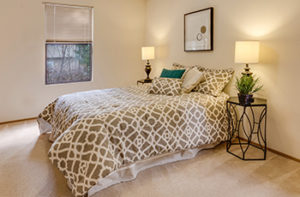 New cream colored carpet in master bedroom with queen size bed and decorative shams.