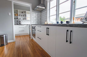 Kitchen remodel showcasing white cabinets and new laminate flooring.