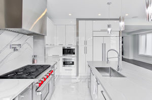 Ultra-modern, all-white kitchen design with large format tiles and granite accents.