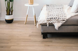 Cool toned laminate plank flooring in a modern bedroom design.