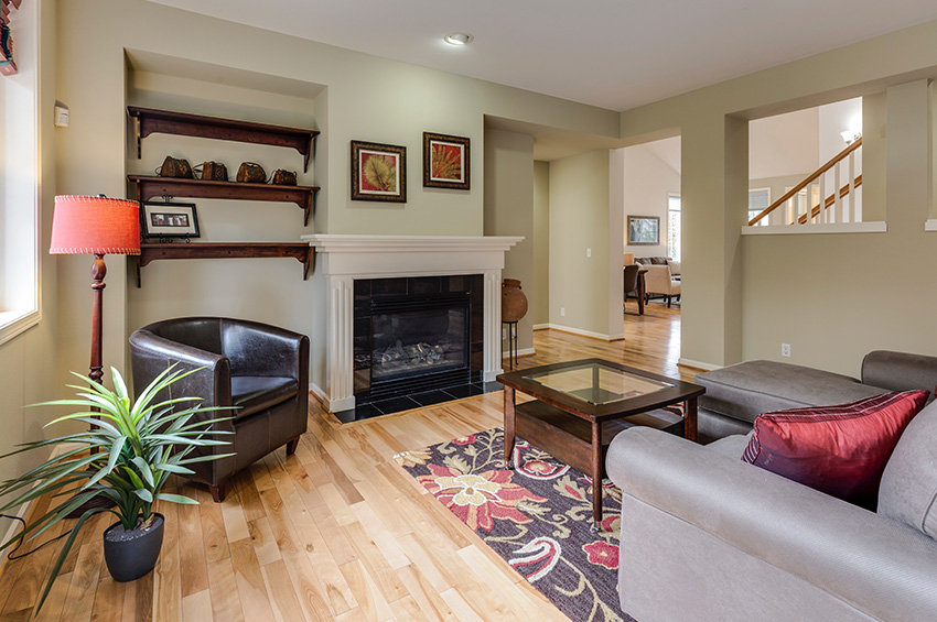 Laminate flooring in the living room of a Portland bungalow with a white fireplace.