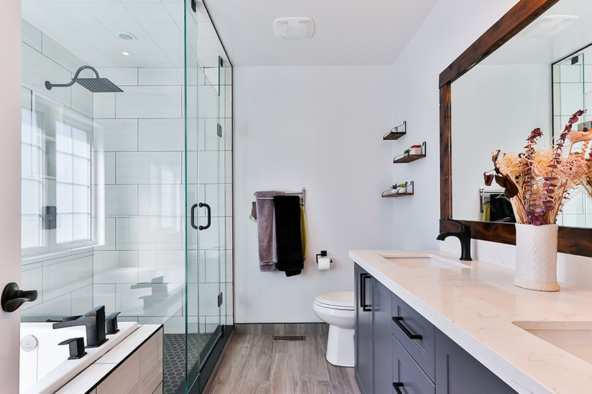Newly remodeled spa-like bathroom with gray toned luxury vinyl plank flooring.
