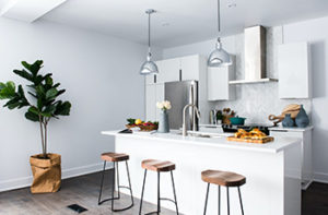 Grey-washed LVP is the flooring in this small, contemporary kitchen that features a white island, three stools, hanging light fixtures, and a stainless steel range hood.