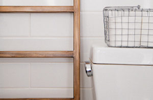 White porcelian tile walls are featured in a small bathroom with a basket of towels.
