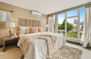 Warm beige carpet with tan area rug in a master bedroom