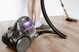 Woman is vacuuming her vinyl flooring using a purple handheld vacuum