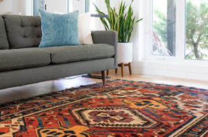 A brightly colored area rug is placed in the living room near a gray couch adding fo a chic bohemian look