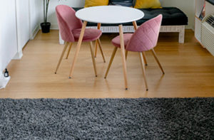 A grey microfiber area rug has been placed on a hardwood floor near a small tulip table with two pink chairs.