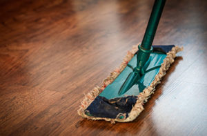 Close up of a traditional mop on dark, wood-like looking vinyl flooring
