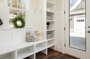 Waterproof wood-like vinyl flooring is in a small mudroom with white built-in cabinets and bench.