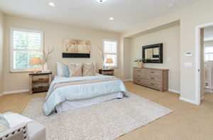 A plush white area rug has been placed on beige carpet in a bedroom, which creates a warm and welcoming look