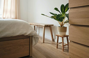 Wood-like light oak looking laminate flooring in a small bedroom