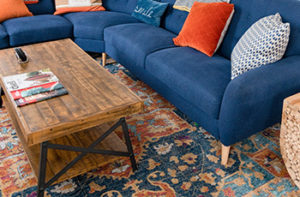 A brightly colored silk Oriental rug lays under a blue couch and rustic wood coffee table.
