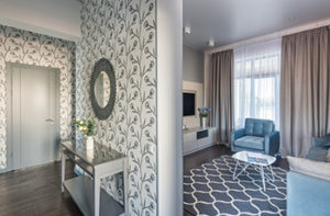 A grey door opens to two beautifully designed rooms that are divided by a wallpapered wall.
