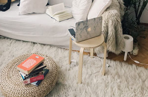 A white shag area rug is next to a white couch where a laptop is open on the table next to it.