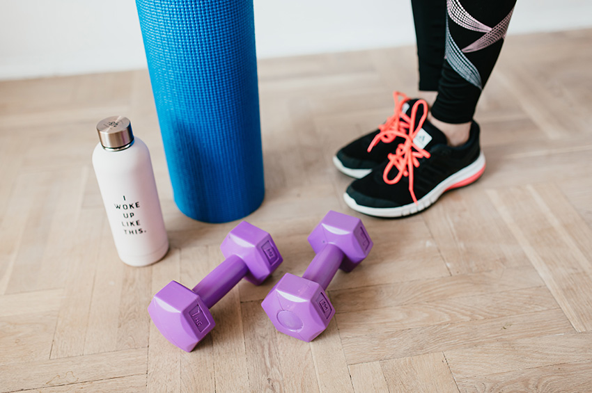 A woman in workout clothes and tennis shoes stands on light oak floors with a yoga mat, weights and pink water bottle