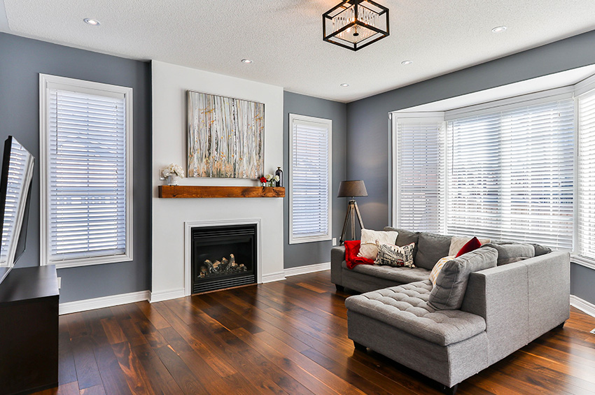 Clean and modern living room features wood-like LVT flooring, gray walls, white brick fireplace with art above the mantle and a grey L-shaped couch.