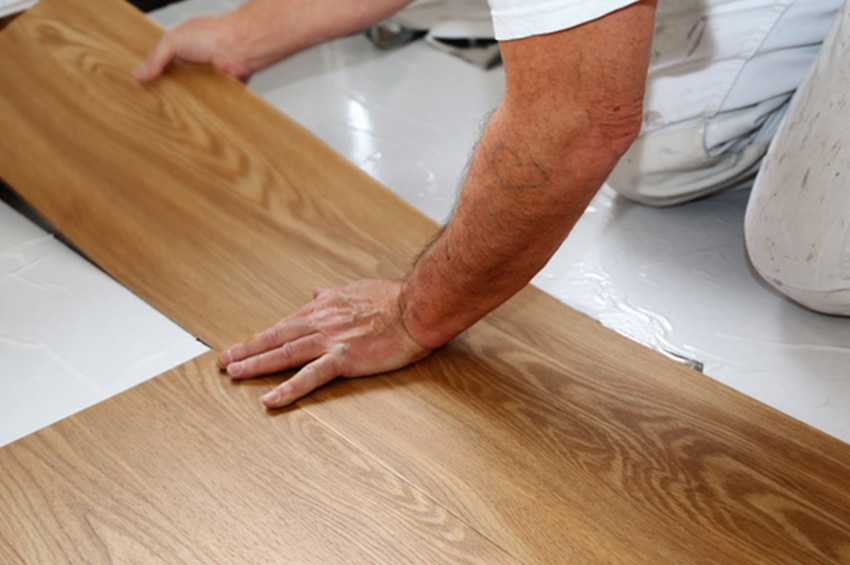 A man works to install remnant LVP flooring in a home.