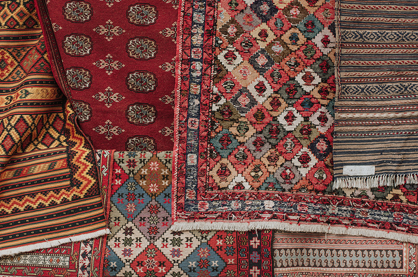 Seven area rugs have been laid on top of each other and all are brightly colored and have different patterns.